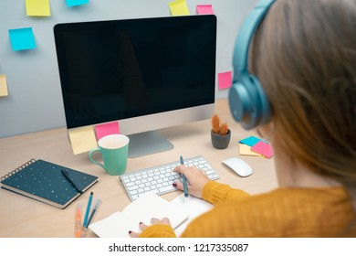 Young professional working on her computer desktop meanwhile is listening music. Creative workplace with a lot of colorful notepads. Morning at a creative studio. Graphic design, mock up screens.  - Shutterstock ID 1217335087