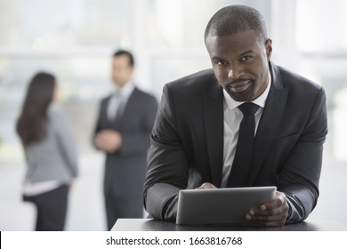 Young professionals at work. A man in a business suit, using a digital tablet.