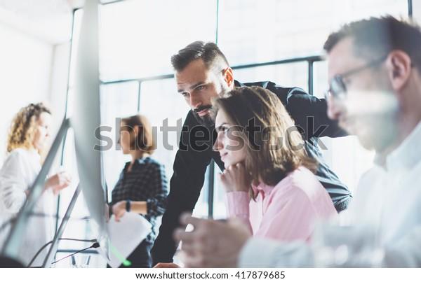 Junge Profis arbeiten im modernen Büro.Projektmanager-Team diskutieren neue Idee.Business Crew arbeitet mit startup.Moderner Desktop-Computer-Tisch, zeigt Präsentation.Unscharf, Film-Effekt.