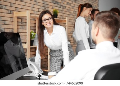 Young professionals working at table in office