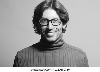 Young professor concept. Portrait of mature man standing over light gray background. Long wavy hair. Close up. White shiny smile. Text space. Studio monochrome shot