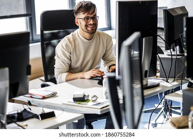 Young programmer sitting at the desk in his office and working .He talk with someone and smiling.