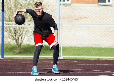 A young and promising streetball player is training in an outdoor sports field. Athletic and active lifestyle. Bearded guy basketball player dribbles during the game, dribbling and feints.