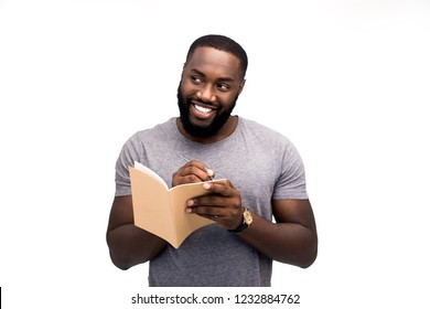 A young promising writer writes in his notebook a draft outline for new poetic or prose literary works. He dreamily looks away, under the influence of inspiration
