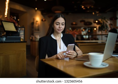 Young prosperous business woman online searching information on account via mobile phone while sitting in luxury restaurant during work break. Female jurist using cell telephone for chat in internet