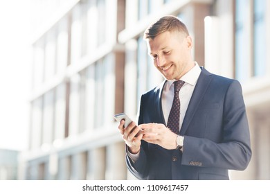 Young prosperous businessman chats online or reads information via cell phone, connected to wireless internet, poses against urban background outdoor, has happy expression. People and wok concept