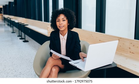 Young prosperous female entrepreneur in trendy formal wear looking at camera, smiling woman economist holding paper with successful ideas for business while sitting at desk with laptop device