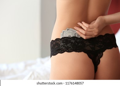 Young prostitute with earned money in brothel, closeup