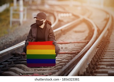 A young Protestant woman sits on a railway wearing black clothing, a mask and gloves, holding a poster with an image of the LGBT flag