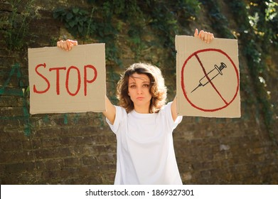 Young protesting woman in white shirt and jeans holds protest sign broadsheet placard with slogan 'Stop' and syringe sing as a symbol of vaccine for public demonstration on wall background