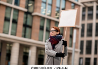 Young protestor with placard demanding raise of salary during demonstration