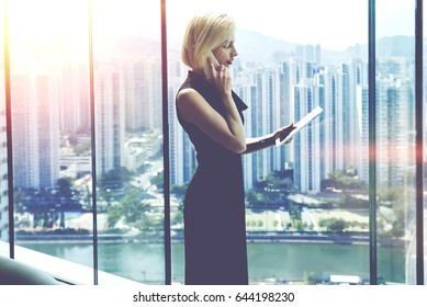 Young proud businesswoman is talking on her mobile phone with client and reading order on digital tablet, while is standing near office window with view of developed business district in China