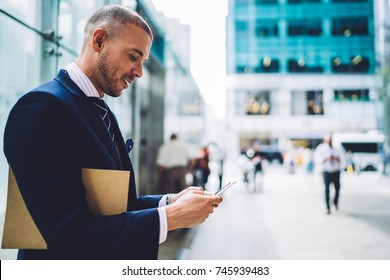 Young proud CEO sending files via application on smartphone standing near copy space for advertising, smiling financial manager satisfied with good news checking email outdoors in business district