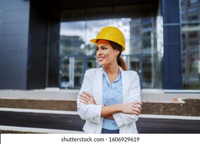 Young proud confident attractive smiling female architect with helmet on head standing with arms crossed in front of building she designed.