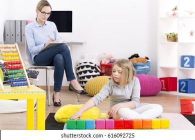 Young psychologist observing little girl playing with building blocks