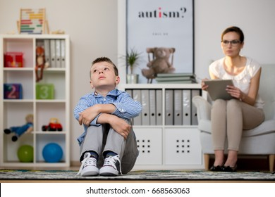 Young psychologist talking to depressed boy in her office