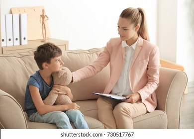 Young psychologist working with little boy in office