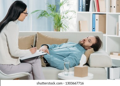 young psychotherapist in eyeglasses writing on clipboard and looking at upset bearded man lying on couch