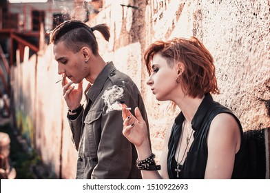 young punk rock couple smokes in the sunset after an argument, human relations concept