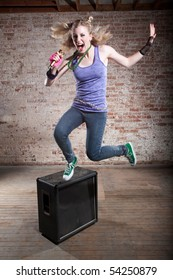 Young punk rocker jumps from a speaker in front of a brick background