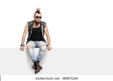 Young punk rocker with a Mohawk hairstyle and a leather vest sitting on a panel isolated on white background