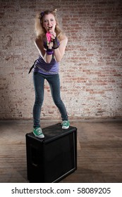 Young punk rocker on a speaker in front of a brick background
