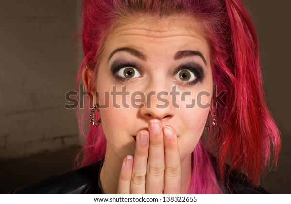 Young punk rocker in pink hair with hand on mouth