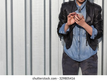 young punk style blond lady leaning on wall and using her mobile phone