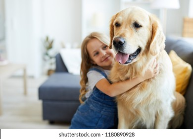 Young purebred labrador and his little friend embracing him at home