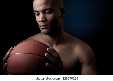 young purposeful black athlete holding basketball ball isolated on gradient blue background