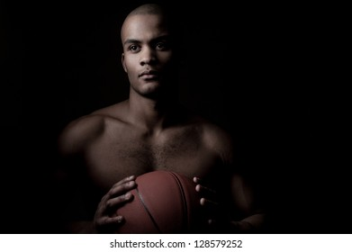 young purposeful black athlete holding basketball ball isolated on black background