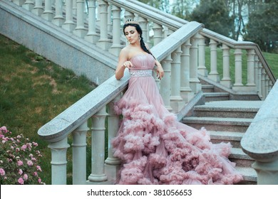 The young queen in a lush pink ball gown standing on the stairs of the castle.