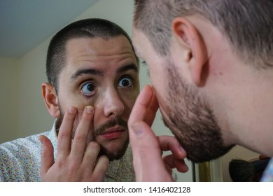 Young queer man uses contact lenses in front of the mirror, doing funny faces and using the pointing finger to put the lense into the eye. He doesn't use glasses, as he prefers to avoid the nerd look.