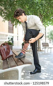 Young quirky businessman pulling up his socks while stepping on a wooden bench in the city, outdoors.