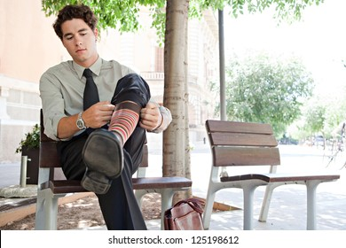 Young quirky businessman pulling up his socks while sitting on a bench in the city, outdoors.