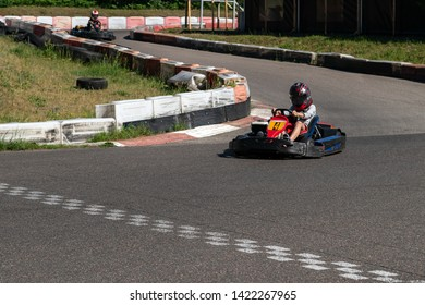 Young racer at go-kart racetrack circuit championship crossing the finish line. Racer with a helmet competing on karting racetrack, fun youth activity