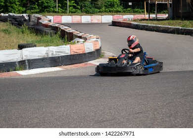 Young racer at go-kart racetrack circuit championship. Racer with a helmet competing on karting racetrack, fun youth activity