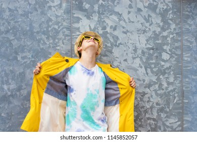 young with raincoat and glasses in urban metallic background, autumn