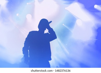 Young rap singer with mic in hand singing popular song in stage in bright blue lights.Hip hop artist performing live on scene in music hall.Youth entertainment event in nightclub.Professional vocalist