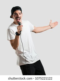Young rapper man happy and motivated, singing a song with a microphone, presenting an event or having a party, enjoy the moment