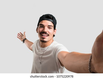 Young rapper man smiling and happy, taking a selfie, holding the camera, excited by his vacation or by an important event, cheerful expression