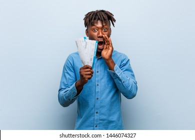 Young rasta black man holding an air tickets shouting excited to front.