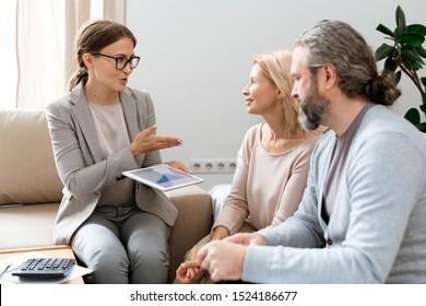Jeune consultante en immobilier avec tablette expliquant à ses clients les principes du changement de tarif lors de la réunion