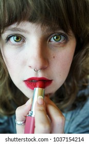 Young real woman applying make up herself