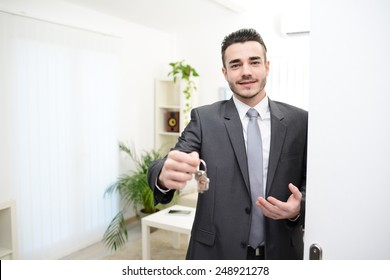young realtor handing house keys in doorway of new house