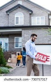 young realtor with sold signboard in front of people moving into new house