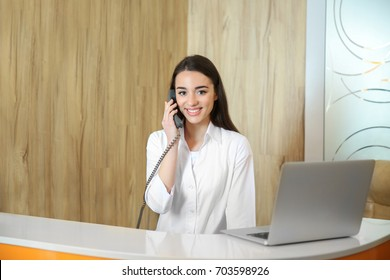 Young receptionist talking on the phone in dental clinic