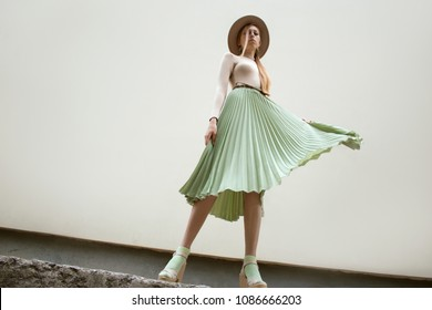 Young red hair girl in hat, dressed in beige blouse and turqoise pleats skirt, on light street backgraund.  Fashion and stylish concept.