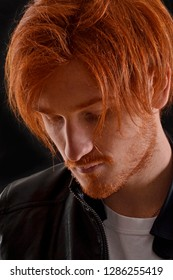 Young red hair stile man portrait on black background.