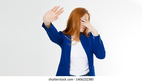 Young red hair woman making a rejection pose and facepalm on a white background.  Negative human emotion face expression feeling body language